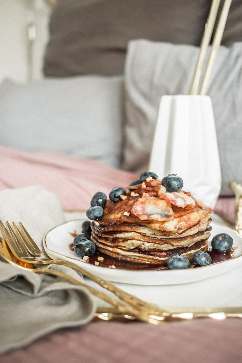 Pancake-Heaven: diverse kleine Pancakes in der Pfanne zubereiten und mit Heidelbeeren, Sirup, angebratenem Bacon und Haselnusskrokant belegen.