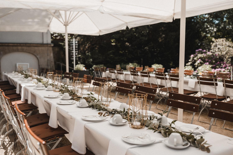 Lange Tafeln mit grünen Eucalyptusläufern und goldenen Laternen als Terrassendekoration bei der Modern Boho Hochzeit