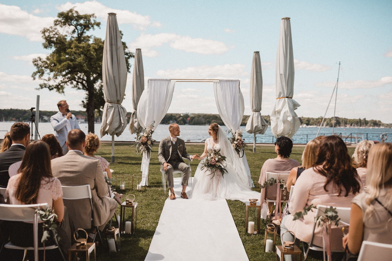 Freie Trauung in der Villa am Wannsee in Berlin mit goldenem Traubogen mit weißem Stoff, Hochzeitsteppich und goldenen Elementen bei der Hochzeit