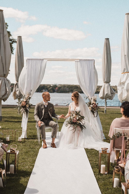 Freie Trauung am See in Berlin mit goldenen Akzenten, Traubogen und Brautpaar