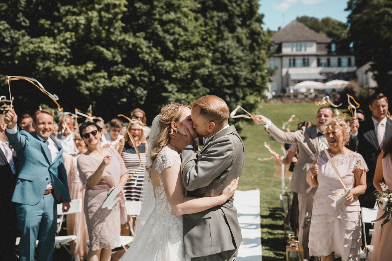 Modern Boho Hochzeit: Der erste Kuss des Brautpaares bei der freien Trauung in der Villa am Wannsee in Berlin mit goldenem Traubogen mit weißem Stoff, Hochzeitsteppich und goldenen Elementen