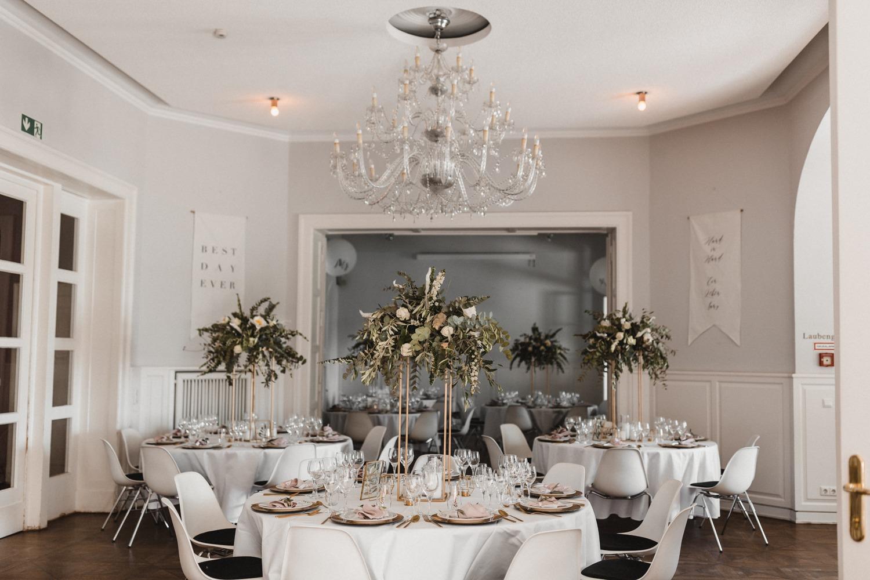 Stilvolle Modern Boho Dekoration zur Hochzeit in der Villa mit runden Tischen, großen Centerpieces in Gold sowie modern und klassischen Elementen
