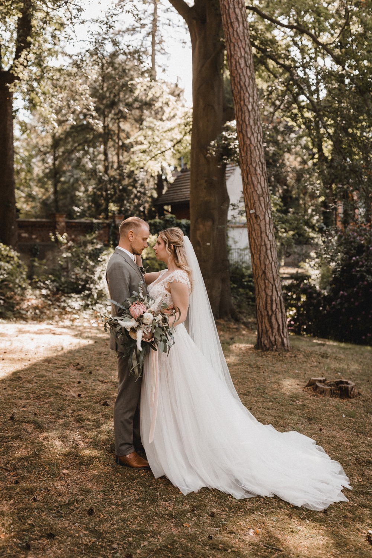 Das verliebte Brautpaar. Der Bräutigam trägt einen graugrünen Zweireiher und die Braut ein Brautkleid in A-Linie mit ausgestelltem Tüllrock und langer Sleppe