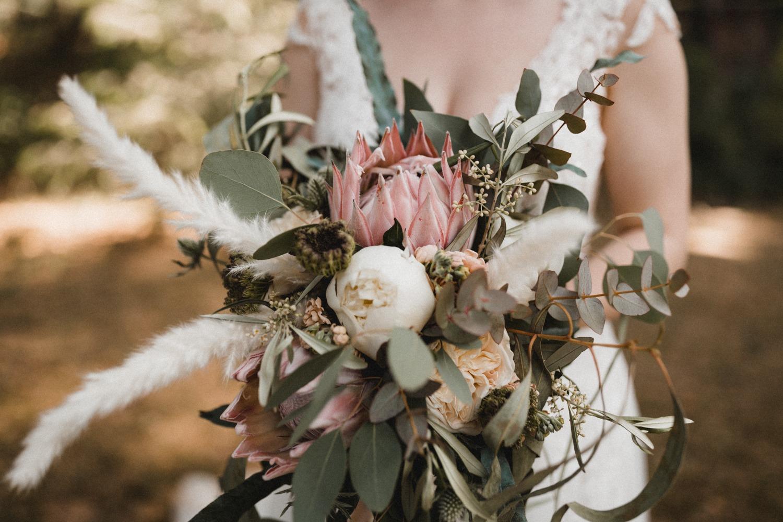 Modern Boho Romance Brautstrauß mit Pfingstrosen, Königsprotea, Oliven und Pampasgras zur Hochzeit