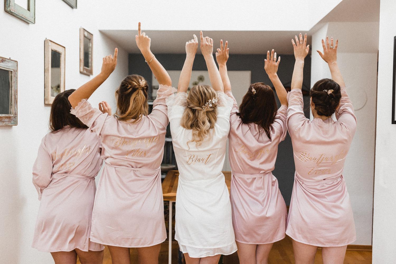 Die Braut und ihre Brautjungfern mit personalisierten Morgenmänteln mit goldener Schrift bei der Hochzeit