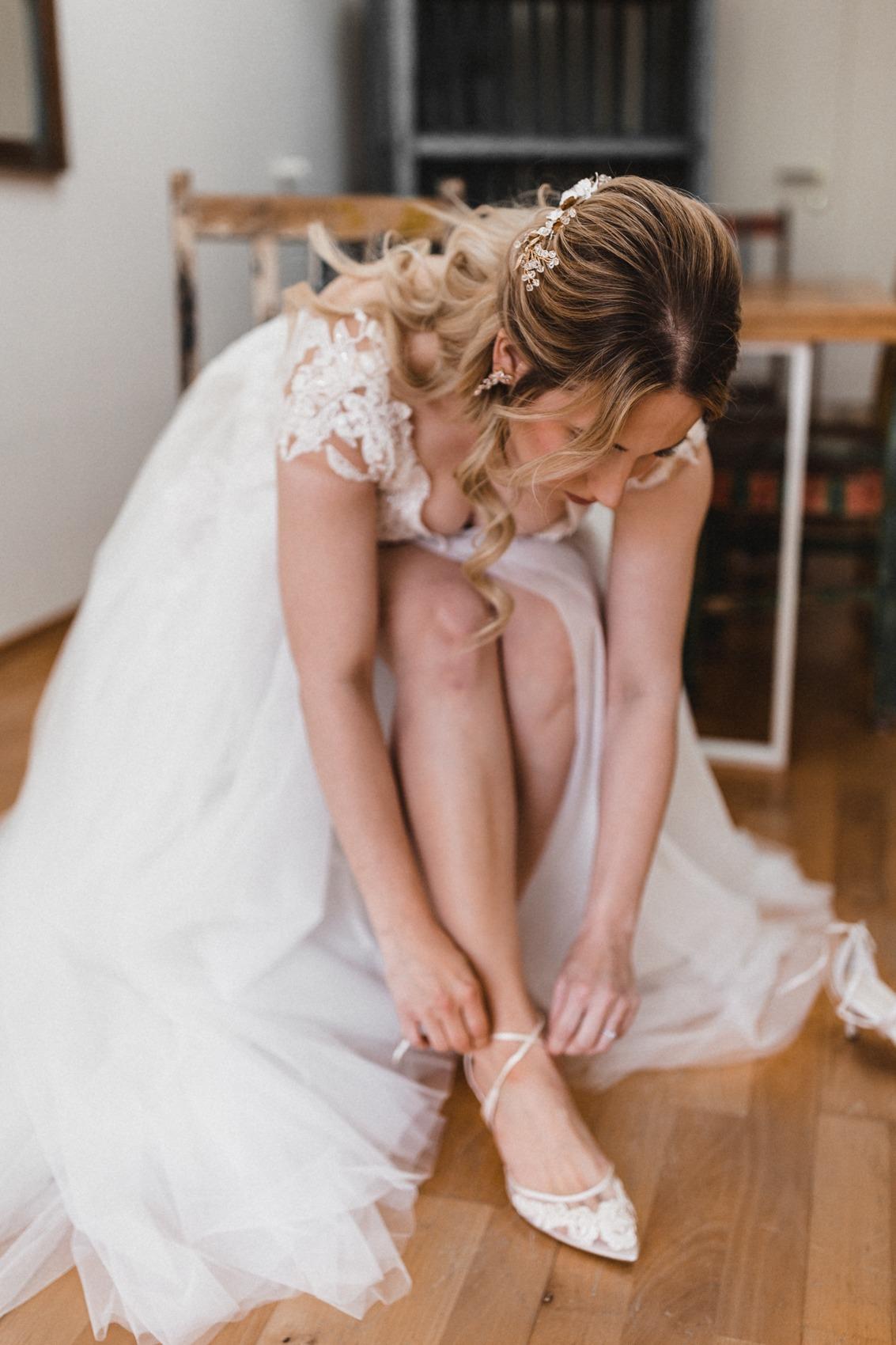 Die Braut in ihrem Brautkleid mit großer Tüllschleppe und Kitten Heels aus Spitze und Seide von Bella Belle