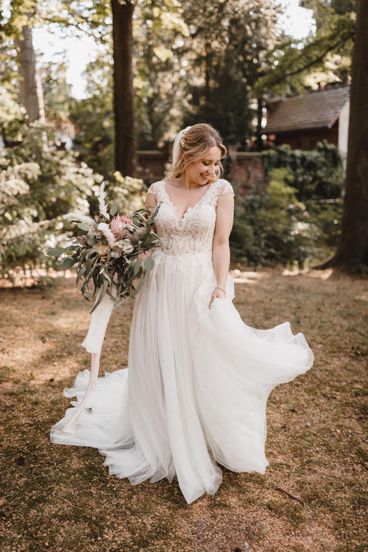 Glückliche Braut in A-Linien Brautkleid mit einem Traum aus Tüll und einer langen Schleppe