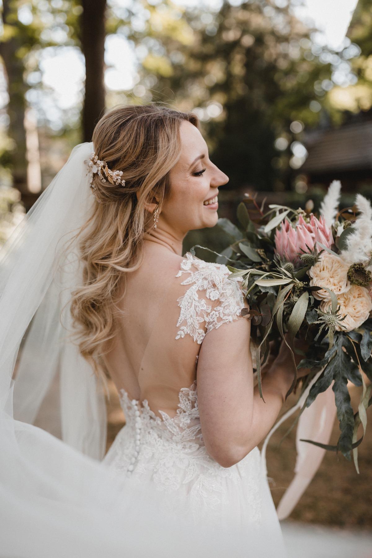 Glückliche Braut mit tiefem Rücken und romantischen Brautkleid mit Schleppe und halboffenem Haar mit Headpiece und Brautstrauß