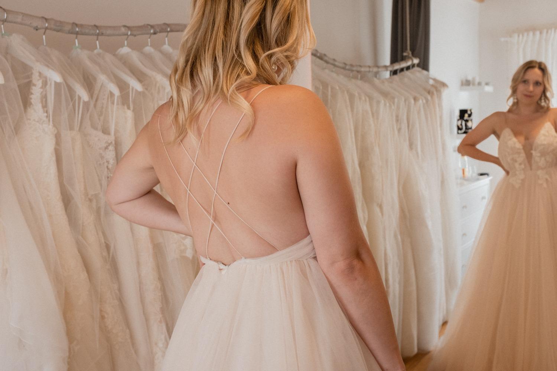 Der Blick der Braut in den Spiegel beim Brautkleid kaufen