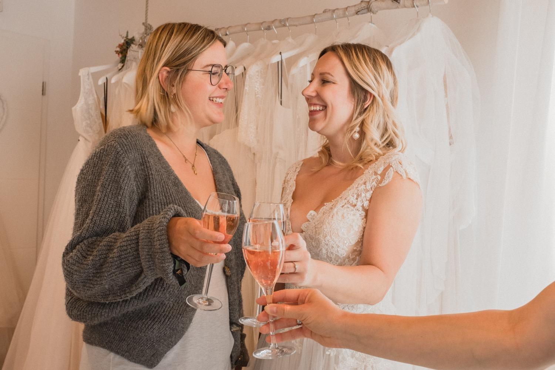 Braut mit Brautjungfer beim Anstoßen im Brautladen