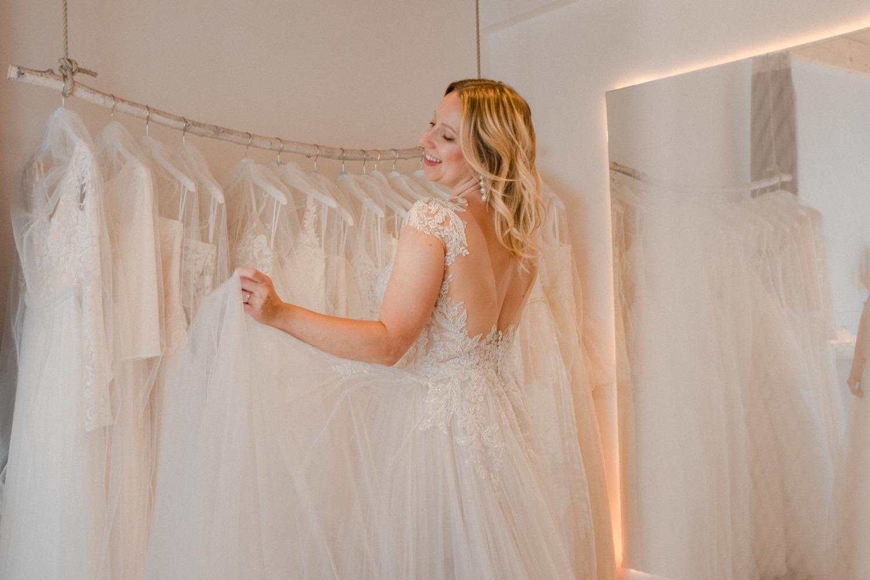 Glückliche Braut-to-be und rückenfreies Brautkleid kaufen im Brautzimmer in Berlin