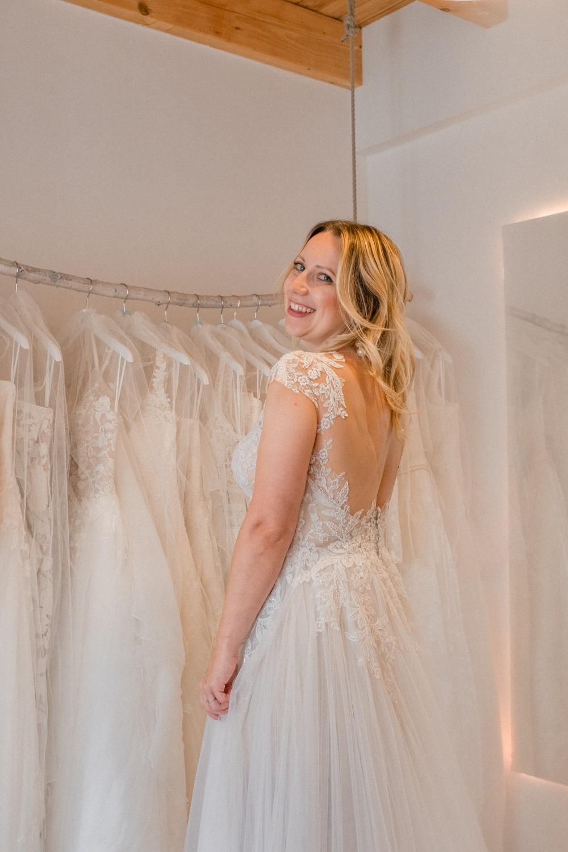 Glückliche Bride-to-be in ihrem Hochzeitskleid im Brautladen