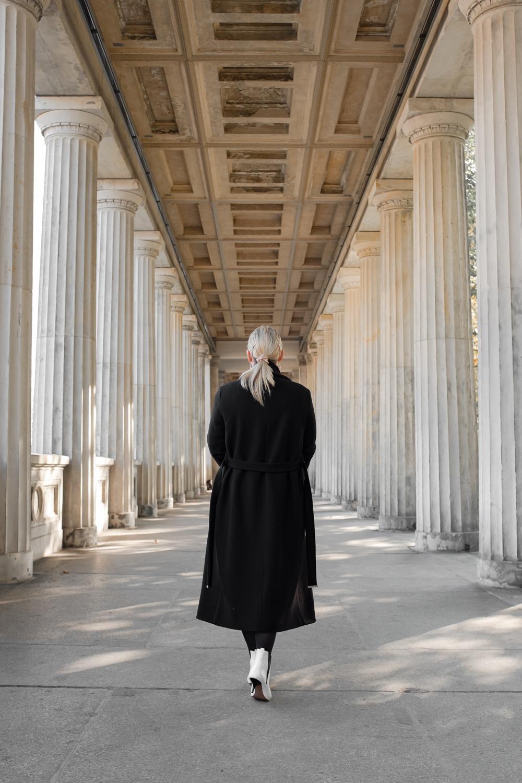 Laufende Frau auf der Berliner Museumsinsel zwischen den Säulen AHOX Mantel Kollektion