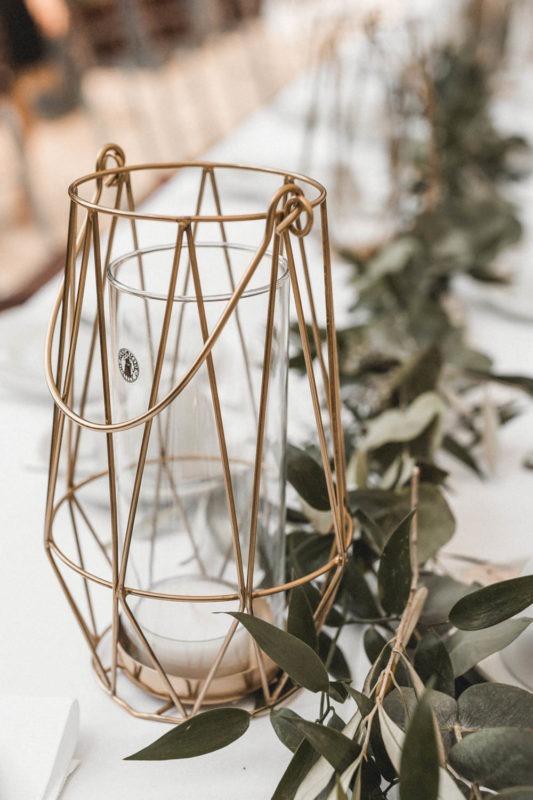 Geometrische Laternen und Olivengirlande als Tischdekoration für die lange Hochzeitstafel