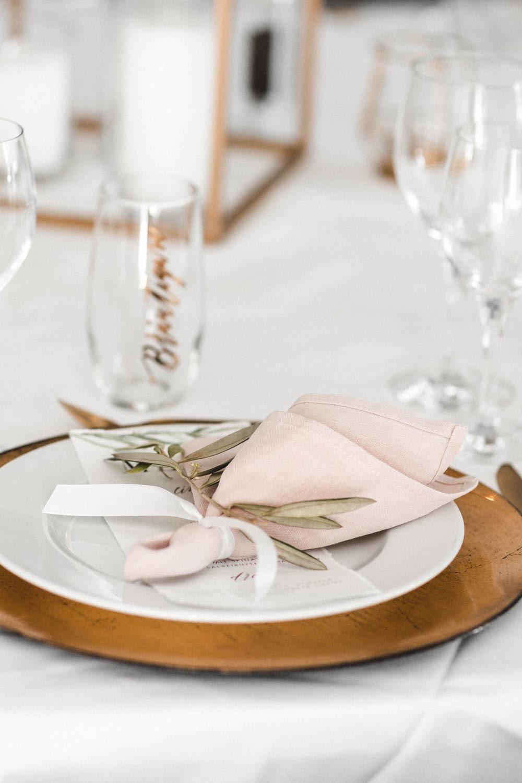 Unsere nachhaltige Hochzeitsdekoration der runden Tische mit goldenen Platztellern, blushfarbenen Leinenservietten, goldenem Besteck und personalisierten Gläsern als Gastgeschenk und gleichzeitig Namenskärtchen.